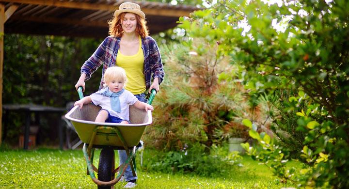 Junge Frau mit Kleinkind in einer Scheibtruhe