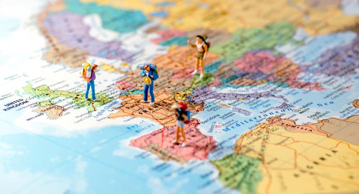 Spielfiguren mit Rucksack stehen auf einer Europalandkarte