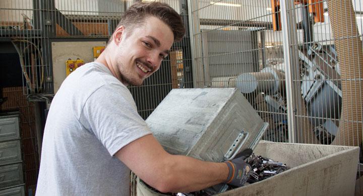 Jugendlicher, der bei der Arbeit eine Metallbox ausleert