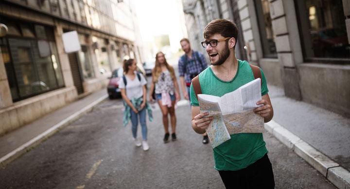Junger Mann mit einem Stadtplan in der Hand