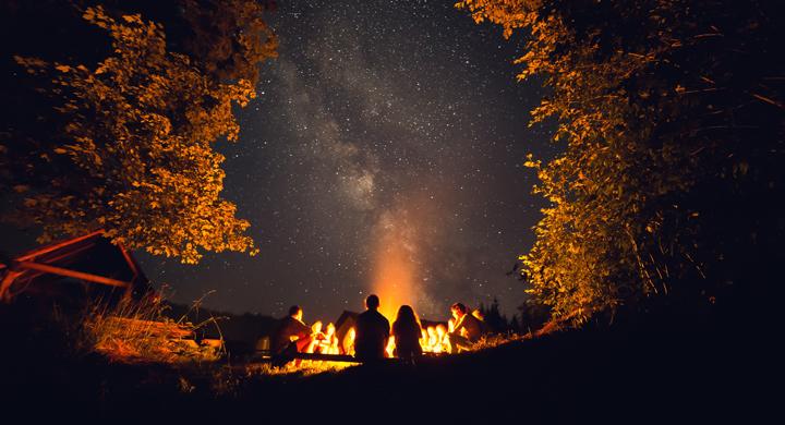 Jugendliche sitzen um das Lagerfeuer.